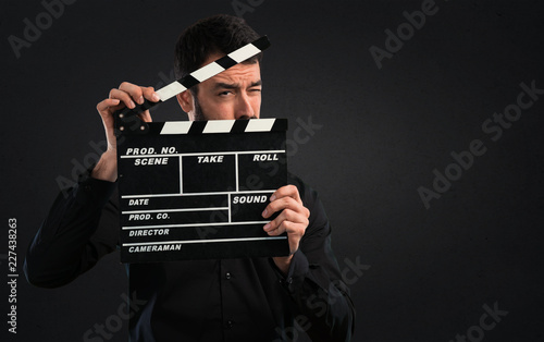 Fotomural Handsome man with beard holding a clapperboard on black background