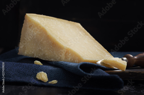 Parmesan cheese on black wooden table with copyspace.