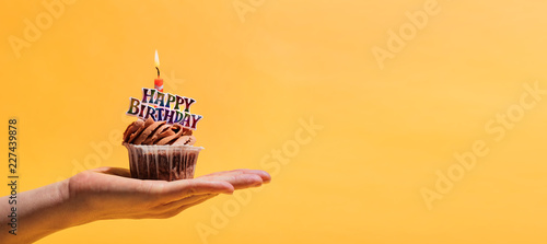 Woman's hand holding decorated birthday muffin. Fototapet