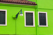 Leinwanddruck Bild - Closed windows with wooden shutters and vintage lamp on green colorful wall in Burano near Venice, Italy