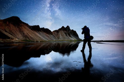 Spoed Fotobehang Reflectie Amazing mountains reflected in the water at starry night. Stoksnes, Iceland. Silhouette of the nature photographer in the frame