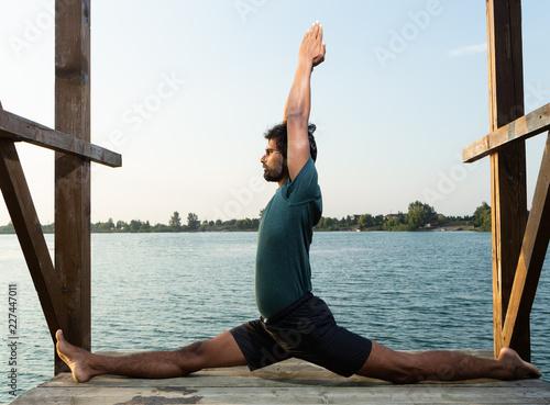 Yoga master doing monkey pose near water. Canvas Print