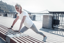 Keep Fit. Sporty Pensioner Expressing Positivity And Looking Downwards While Stretching Body
