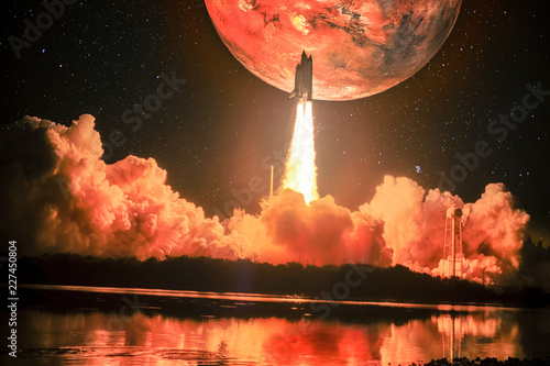 Lighting up the night sky, as well as the water nearby, spacship blazes into the Mars mission. Huge red Mars is on the night sky surrounding by galaxy. Elements of this image furnished by NASA.