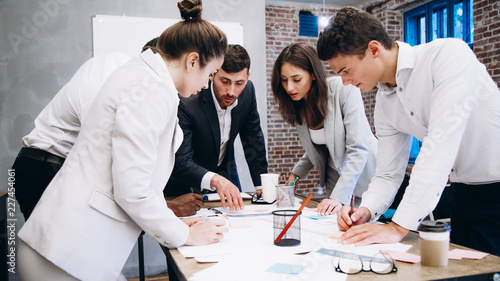 Fototapety, obrazy: Morning meeting. Group of five young people discussing something while sitting at the table in office together. startup