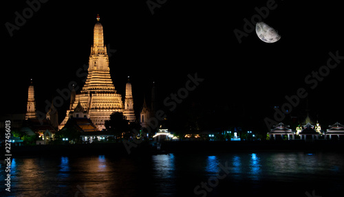 Wat Arun Buddhist Temple in Bangkok at night with moon