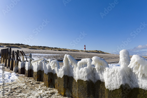 Germany, Schleswig-Holstein, Sylt, beach, frozen breakwater and lighthouse in winter