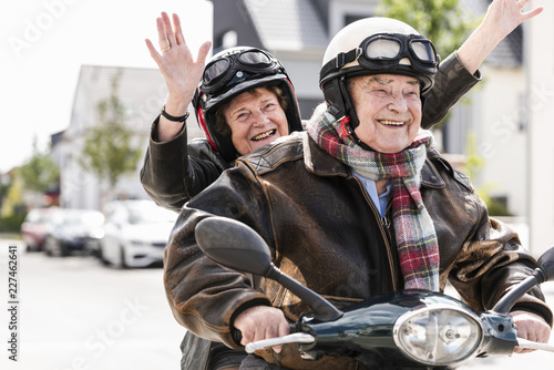 Happy senior couple having fun, riding motor scooter and waving