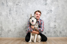 Young Bearded Man Hanging Out Out With His Husky Dog. Hipster Male Wearing Checkered Flannel Shirt And Grey Tank Top Spending Quality Time With Four Legged Pet Friend. Close Up, Copy Space, Background