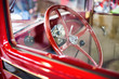 Detail of a red oldtimer car interior (steering wheel and the very simple dashboard) from outside