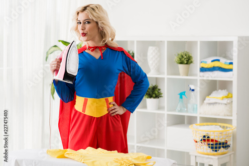 Cuadros en Lienzo Portrait of young attractive blond female maid in superwoman costume standing by