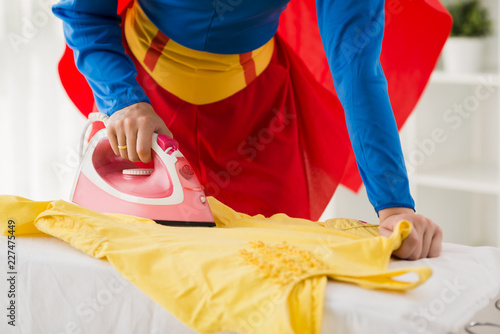 Anonymous woman wearing superwoman costume ironing clean yellow dress on ironing Canvas Print