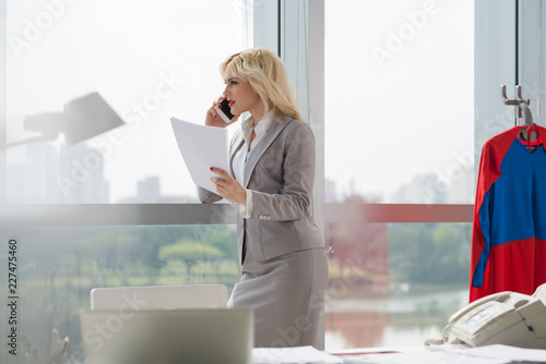 Fotomural Young beautiful female manager talking on mobile phone while standing by window