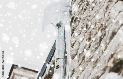 Fotografia, Obraz  season, housing and winter concept - icicles hanging from building drainpipe