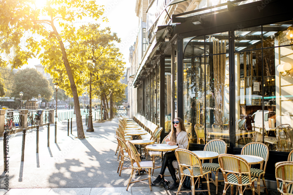 Fototapeta Street view on the traditional french cafe with young woman sitting outdoors during the morning light in Paris