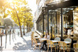 Street view on the traditional french cafe with young woman sitting outdoors during the morning light in Paris