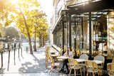Fototapeta Fototapety Paryż - Street view on the traditional french cafe with young woman sitting outdoors during the morning light in Paris