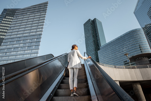 Photo Stylish businesswoman in white suit going up on the escalator at the business ce