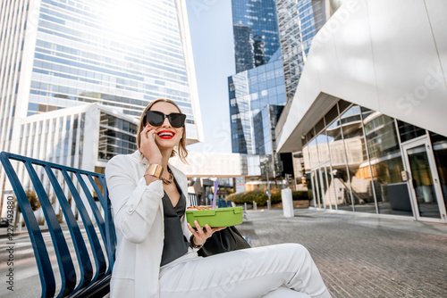 Business woman having a snack with lunch box during a break sitting outdoors at Wallpaper Mural