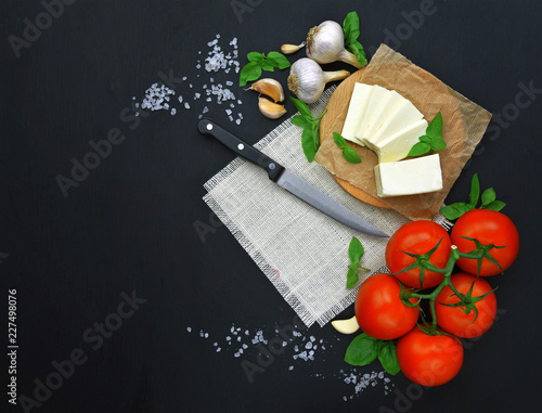 Fresh feta cheese with tomatoes,greens on wooden serving board over wooden background. Food Ingredients, view from above. Healthy food.Top view.