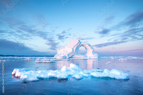 Photogenic and intricate iceberg with a hole under an interesting and colorful sky during sunrise with full moon Fotobehang