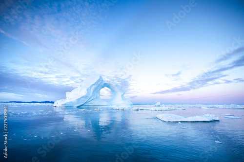 Fotografia  Photogenic and intricate iceberg with a hole under an interesting and colorful sky during sunrise with full moon