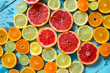 Abstract background of citrus slices. Close-up of fresh orange, tangerine, grapefruit, lime and lemon slices on blue background, citrus slice texture.
