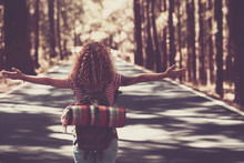 Young Curly Lady Walking In The Middle Of Long Way Road With Forest Around. Freedom And Independence Concept Image For People In Wanderlust That Love To Travel And Enjoy The World And The Distances