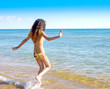 Charming girl runs into the sea water. girl teenager in summer in a swimsuit at sea, vacation