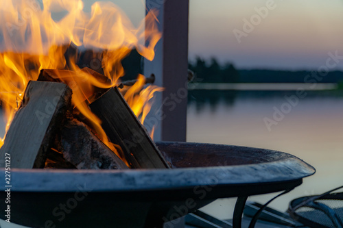 Photo Flammen in einer Feuerschale in der Dämmerung am See