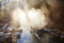 High Angle View Of Woman Relaxing In Hot Spring At Forest