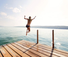 Rear View Of Young Woman Diving Into Lake Against Sky On Sunny Day