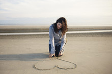 Woman Drawing Heart On Sand At Beach Against Sky