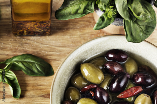 Overhead view of olives in bowl on cutting board