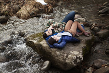 Couple Lying On Rock By River