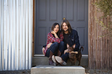 Portrait Of Couple Sitting With Dog Against Door At Backyard