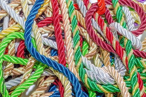 Fotobehang Paradijsvogel bloem Multi-colored braided decorative laces scattered in a mess. Textile manufacture, threads, decor.
