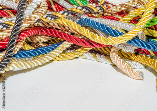 Fotografía  Multi-colored braided decorative laces scattered in a mess