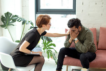 Therapist Cheering Up His Extremely Depressed Patient In Modern Room