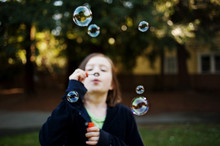 Girl Blowing Bubbles While Sta...