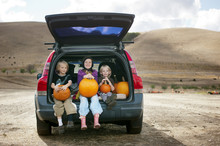 Siblings Holding Pumpkins On Lap While Sitting In Car Trunk