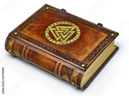 Vintage leather book with gilded Odin's symbol lay down to the table Wallpaper Mural