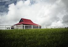 House On Field Against Cloudy Sky