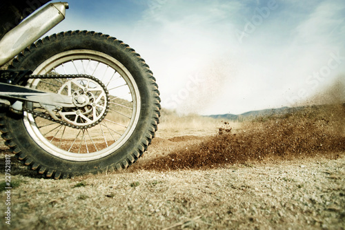 Cropped image of motorcycle on dirt road