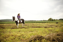Woman Sitting On Horse In Rural Landscape