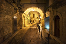 Walkway And Buildings In Old Town Illuminated At Night, Italy