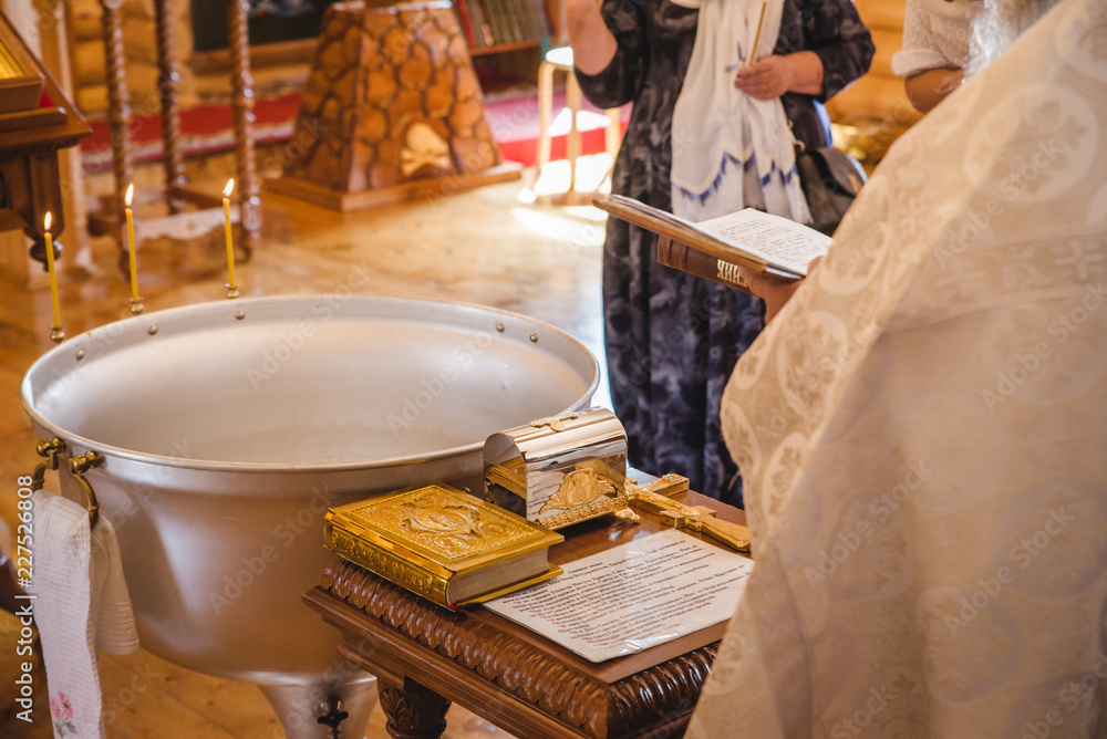 Fototapety, obrazy: Christening ceremony in the Orthodox church, priest lighting candles at children baptismal font, close up