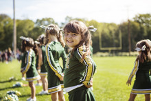 Portrait Of Girl In Sport Uniform Standing In Field With Team