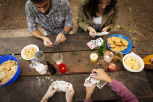 High Angle View Of Friends Playing Cards While Sitting At Picnic Table