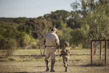 Rear View Of Father And Daughter Carrying Rifles